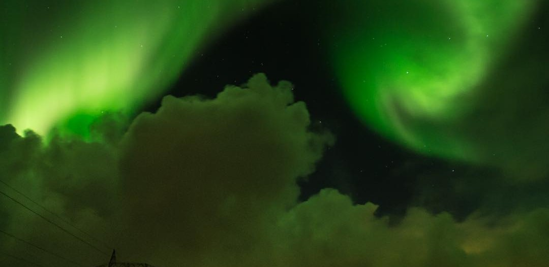 Spectacular northern lights over the highway in Iceland
