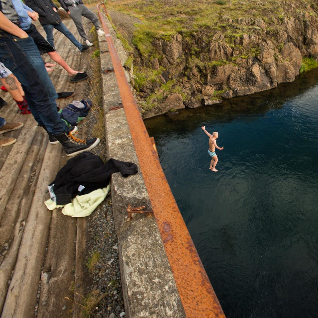 A man jumps off a bridge and into the water below