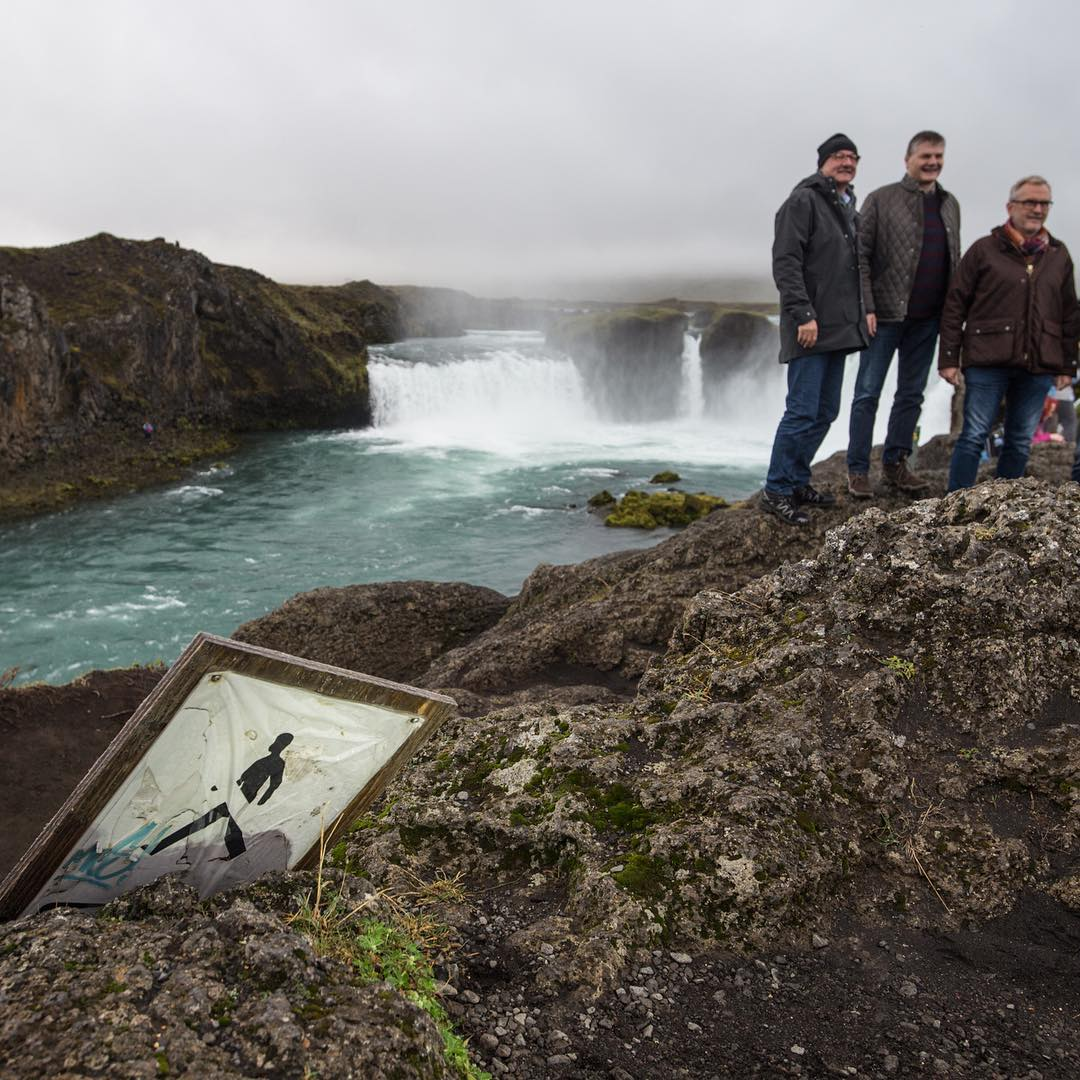 Goðafoss waterfall with a sign in the foreground and men in the background