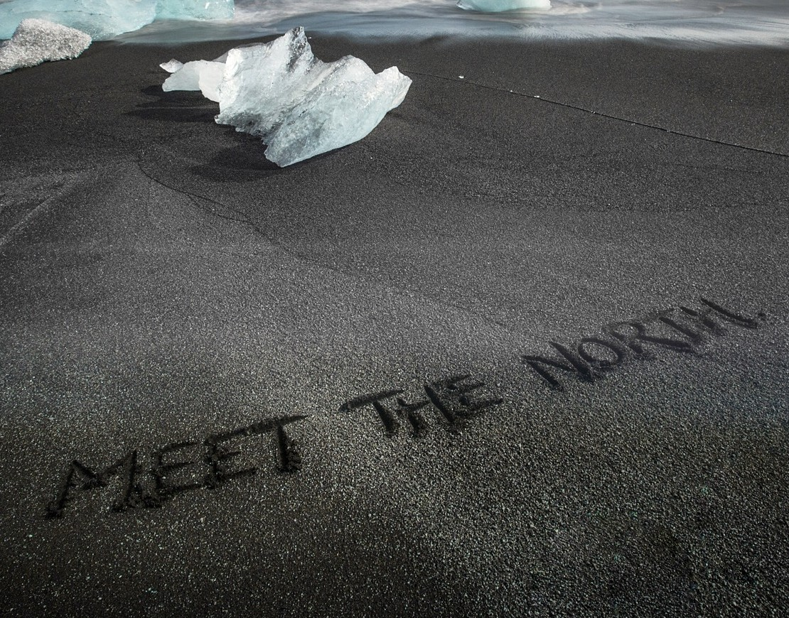 Meet the North written in the black sand beach of southern Iceland