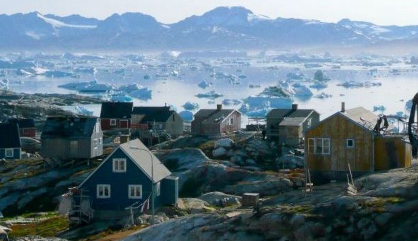 A greenlandic town with sea ice in the background