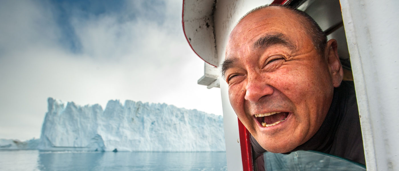 A man smiles widely with his head out of a small portal on a boat, with an iceberg drifting in the distance.