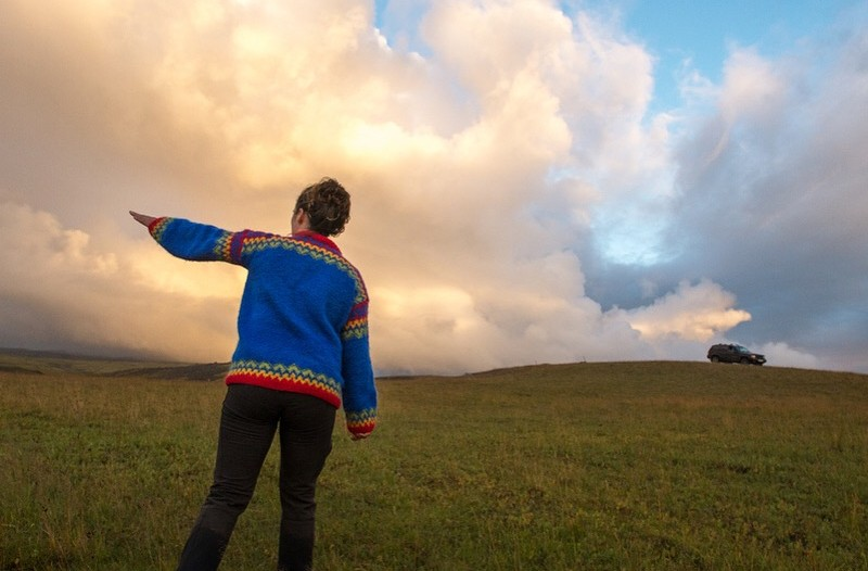 A woman in a blue sweater points the way across a green field