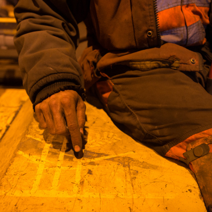 A miner draws a diagram in the coal dust