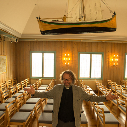 The pastor of Svalbard Kirke stands with his arms wide.