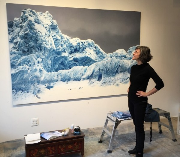 Zaria stands in front of a large pastel drawing of ice