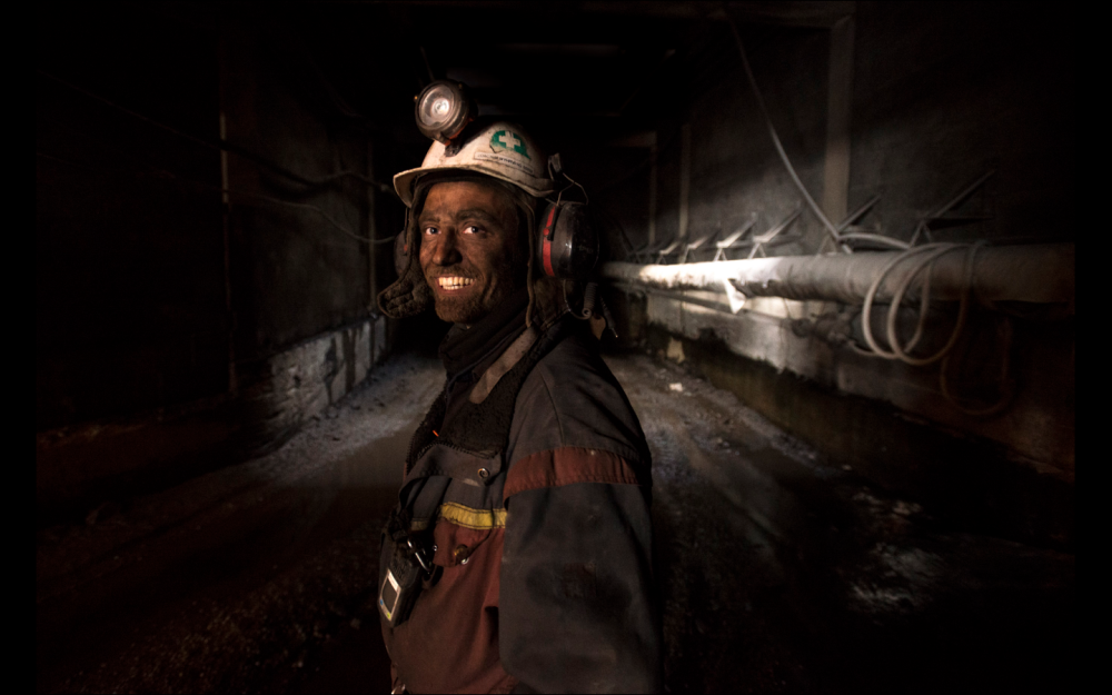 A man smiles below ground, his face covered in coal dust.