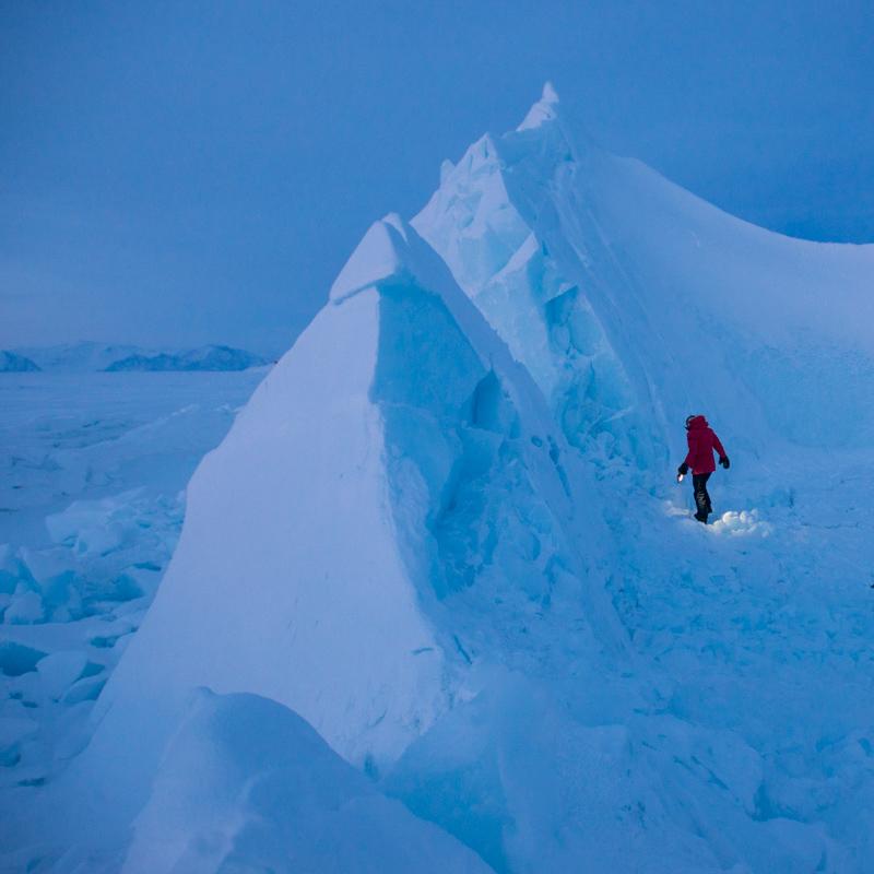 A figure walks beside an iceberg.