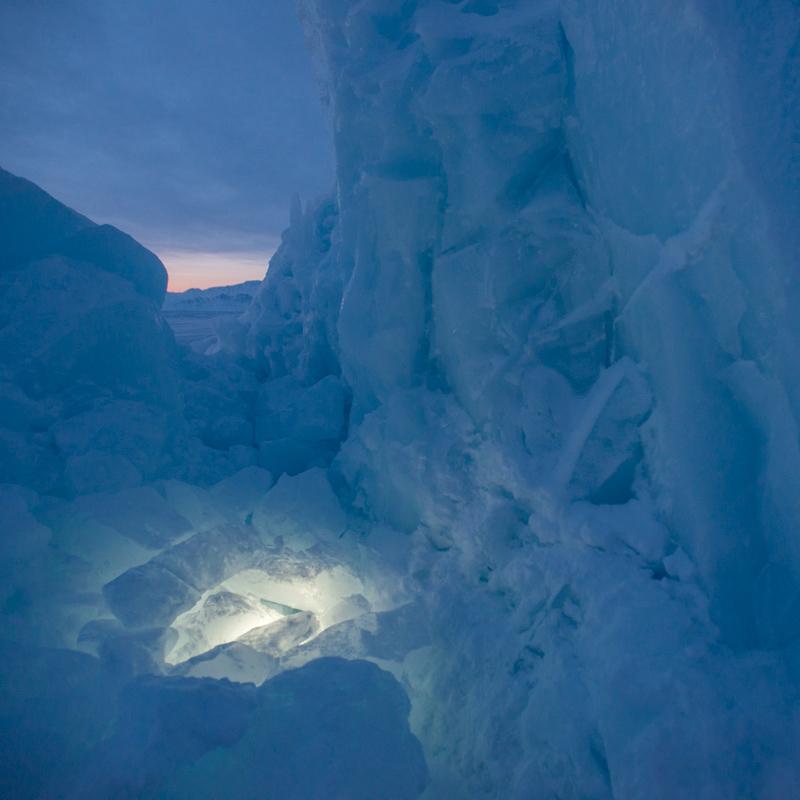 An iceberg, illuminated as the sun sets.