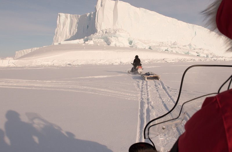 A view over the shoulder of a snowmobile driver following behind a qamutik.