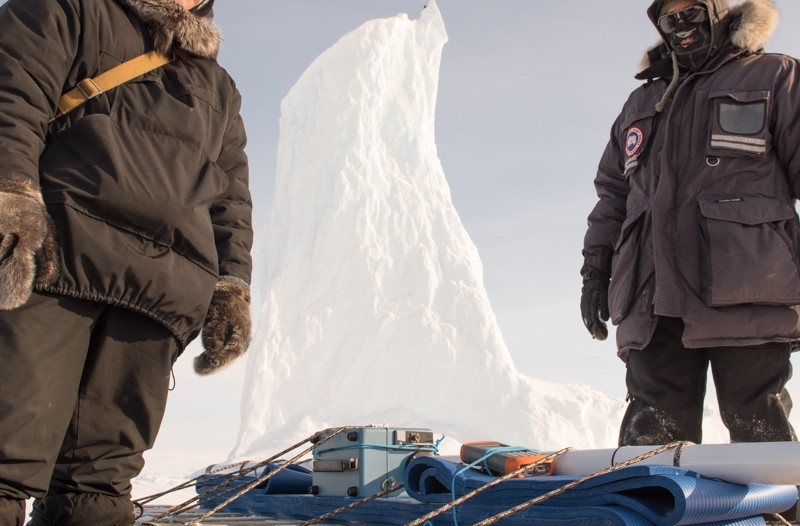 Two men stand beside a sled carrying science equipment.