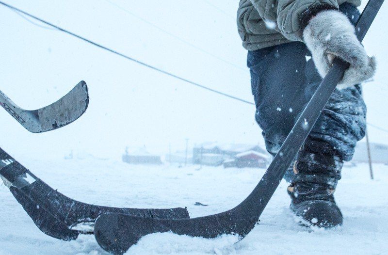 A closeup of a hockey puck amid three hockey sticks in the icy streets of Pond Inlet.