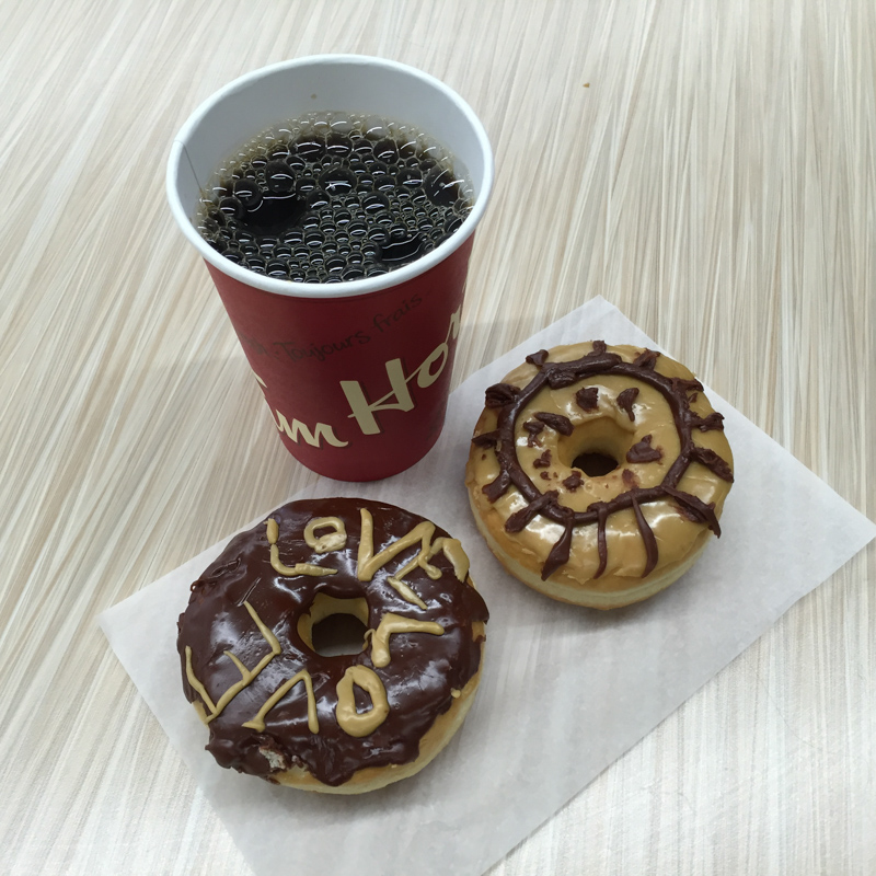 "A Tim Hortons coffee and a donut with the words ""LOVE LOVE"" written across it."