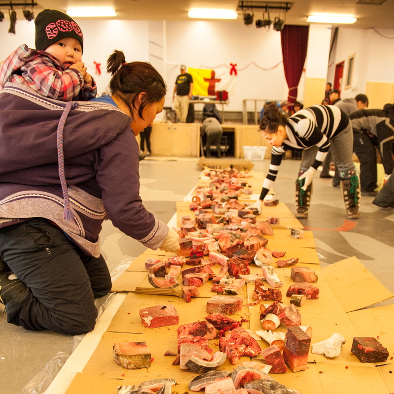 Two women help to prepare and arrange an array of meats.