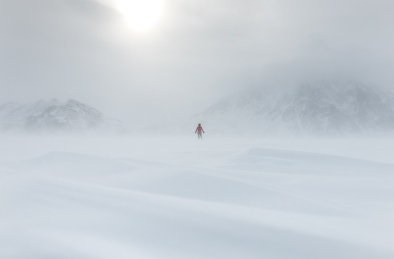 A figure stands in the distance as snow rolls across a plain of sea ice.