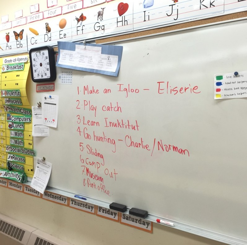 A whiteboard shows a list of activities.