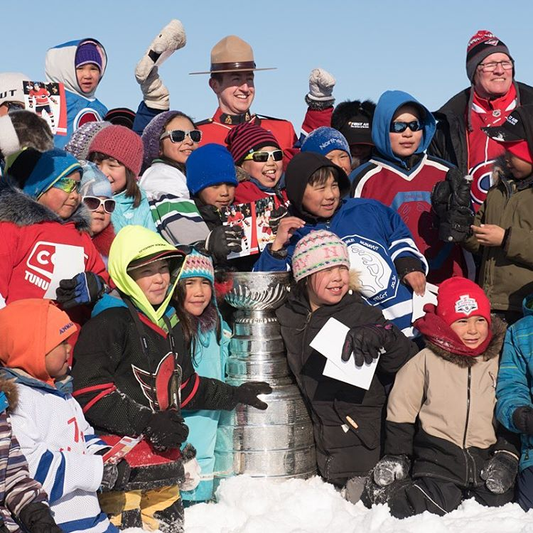 A group of delighted residents pose with the Stanley Cup outside Pond Inlet.