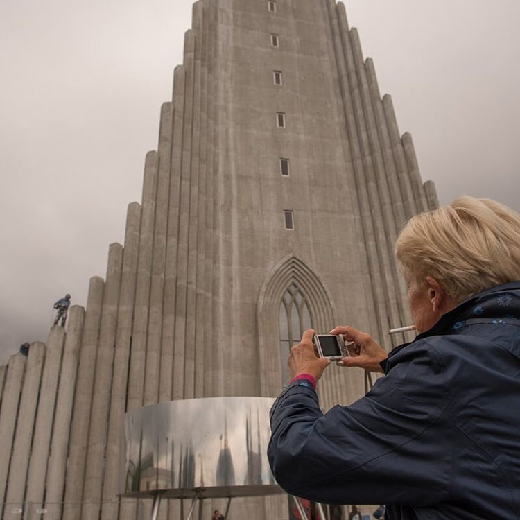A woman photographs a modern statue.