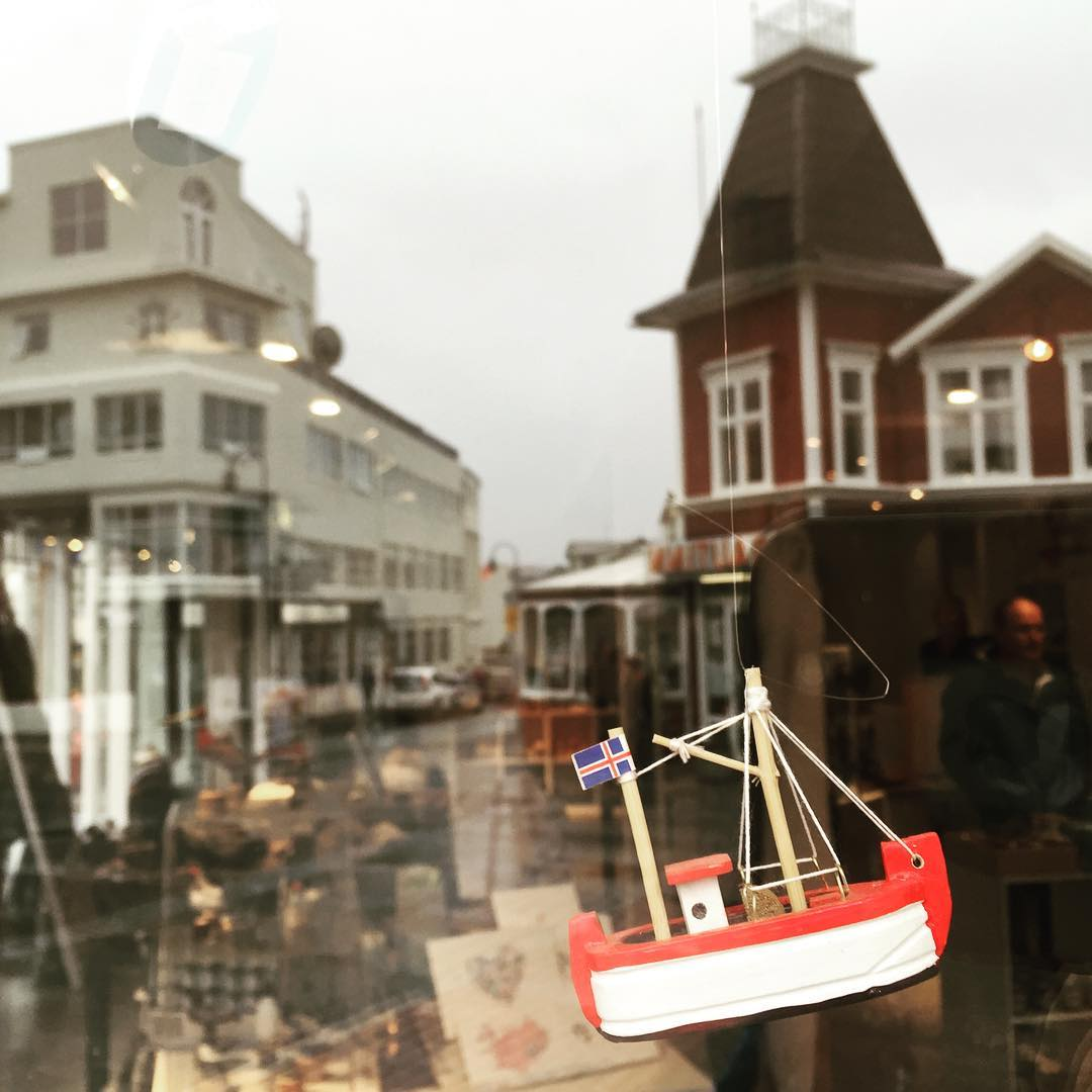 A toy boat hangs in a window.