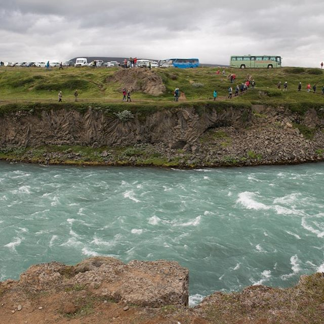 Tourists look on across a beautiful Icelandic river.