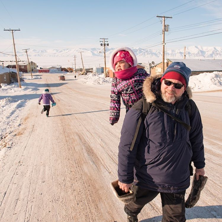 A father walks home with his daughter in Pond Inlet.
