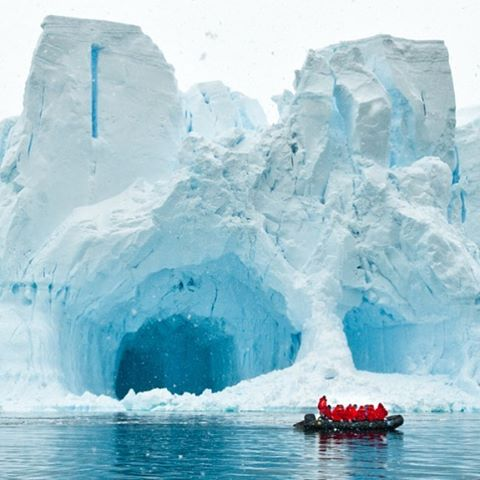 A boat full of people passes a cavernous iceberg.