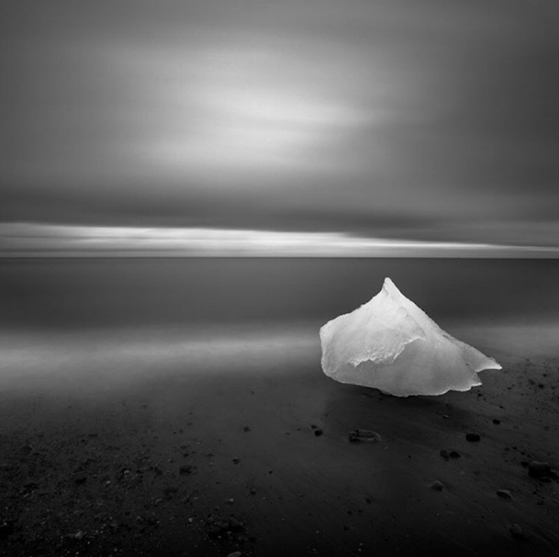 A piece of ice sits on the beach.
