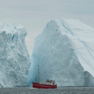 A boat sitting between icebergs in Ilulissat, Greenland.