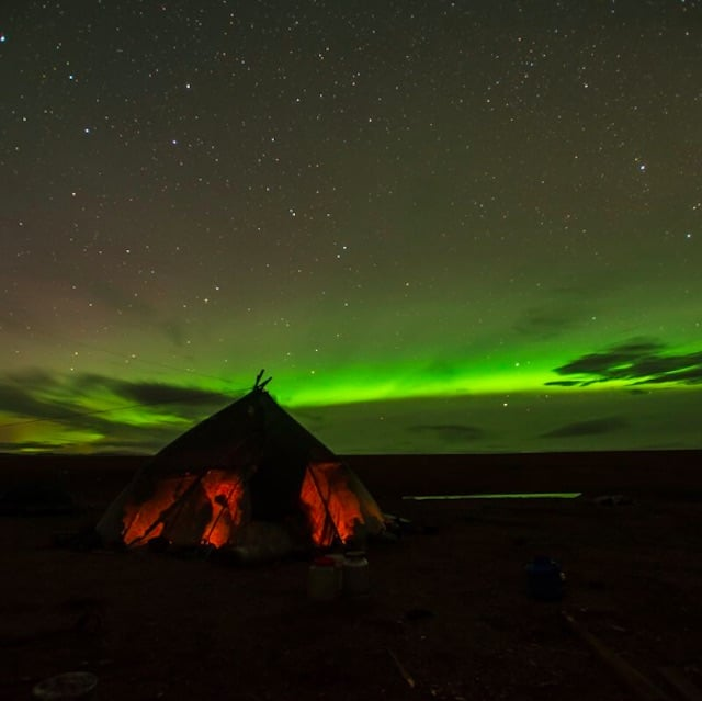 The aurora borealis behind the tent.
