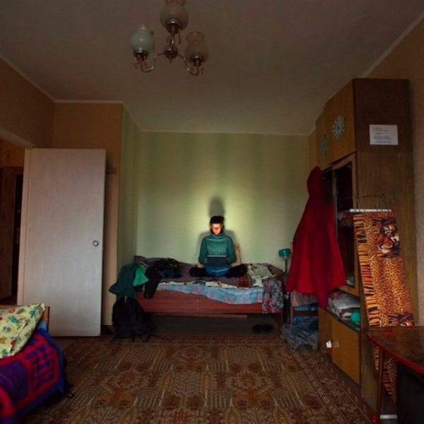 Jenny works on her computer in a hotel room in Russia.