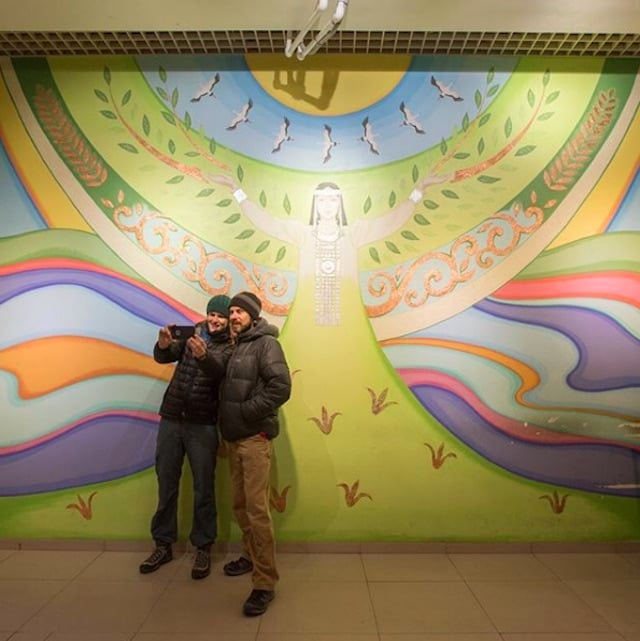 Eric and Jenny stand by a mural in Russia.