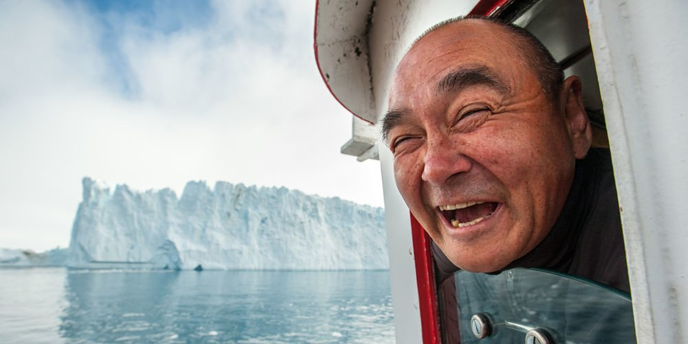 Karl-Ole Kristensen shares a laugh from the bridge of the Else, a fishing boat turned ice tour vessel. Ilulissat, West Greenland.