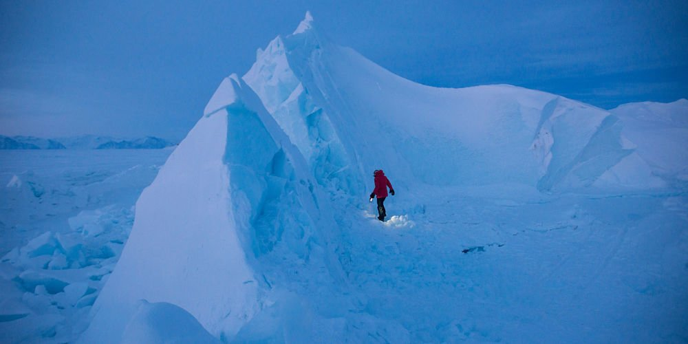 Jennifer Kingsley (Meet the North founder) walks atop an iceberg frozen into the sea ice near the town of Pond Inlet. Northern Baffin Island, Nunavut, Canada. Locals use the glacial ice for fresh drinking water during the winter months.