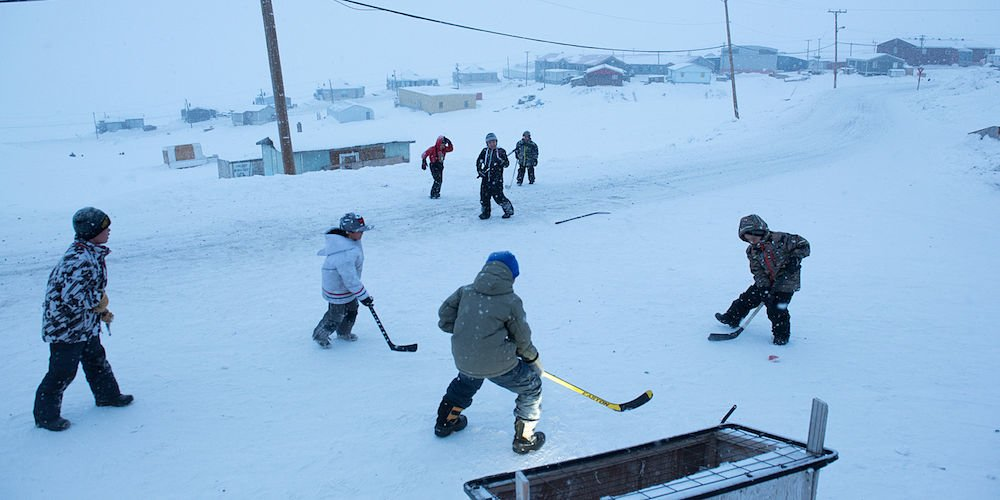 Children from the northern Baffin Island hamlet of Pond Inlet, play hockey in the streets during a -20F spring evening. Nunavut, Arctic Canada.