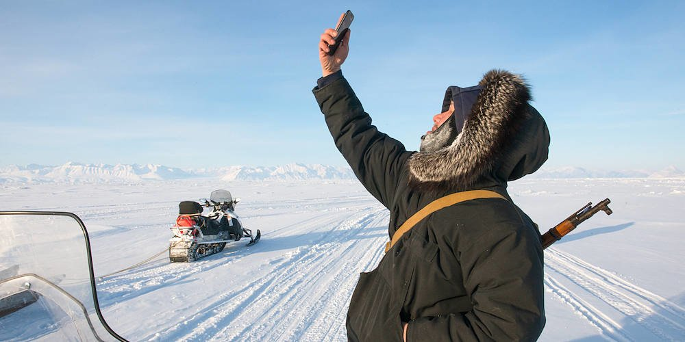 Local SMART ICE coordinator, Andrew Arreak checks his phone while measuring sea ice thinkness near the town of Pond Inlet, Nunavut, Canada.