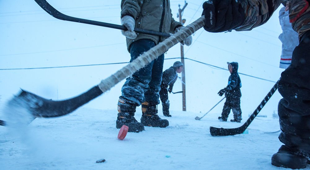 Kids play street hockey in Pond Inlet.
