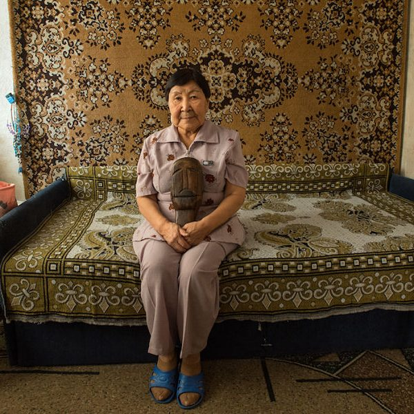 Elizaveta Dobrieva sits in her apartment in Lavrentiya, Chukotka holding the keeper of her clan, a wooden female figure called Yiakunneun.